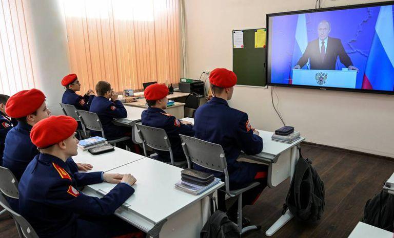 Cadetes da corporação dos Cossacos acompanham o discurso de Putin na televisão nesta quarta-feira, em Rostov do Don