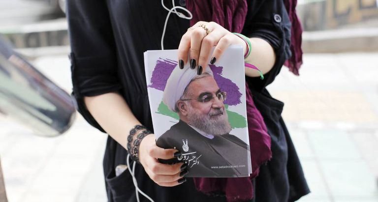 Eleitora mostra a foto de Hasán Rohaní em Teerã.