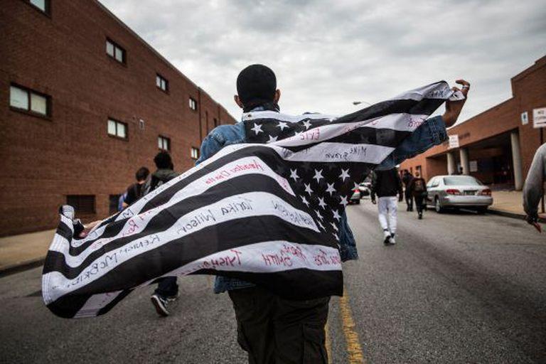 Manifestante leva uma bandeira dos EUA tingida de preto.