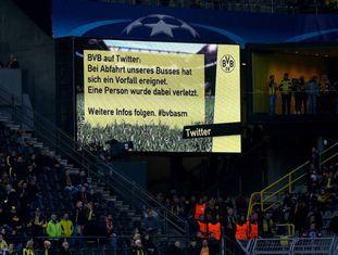 Telão do estádio em Dortmund, na Alemanha, avisa sobre a explosão que feriu o jogador Marc Bartra.