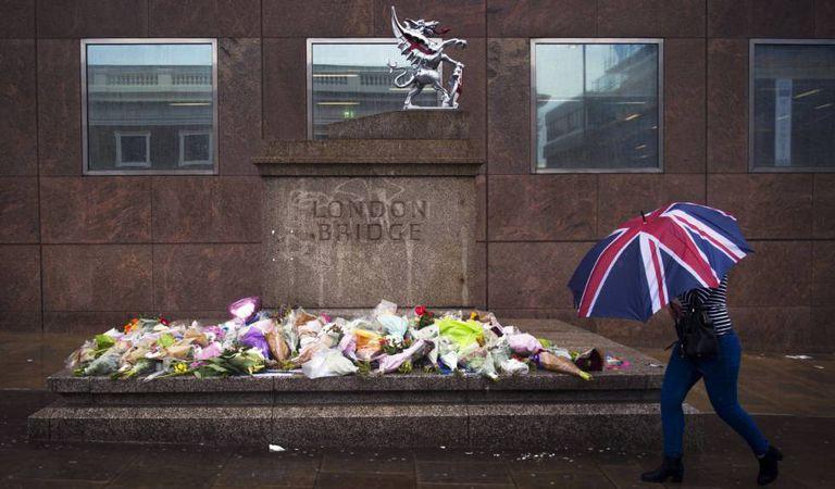 Mulher passa em frente aos ramos de flores deixados em homenagem às vítimas do atentado do sábado na London Bridge.
