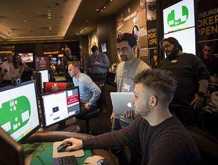 Sandholm, à esquerda, de gravata, e Brown, com um laptop na mão, durante uma experiência do Libratus contra campeões de pôquer.