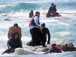 O acidente aconteceu quando, por motivos desconhecidos, o barco encalhou nas rochas, perto da praia de Séfiros, e posteriormente afundou. Na imagem, várias pessoas colaboram no resgate de imigrantes na ilha grega de Rodes.