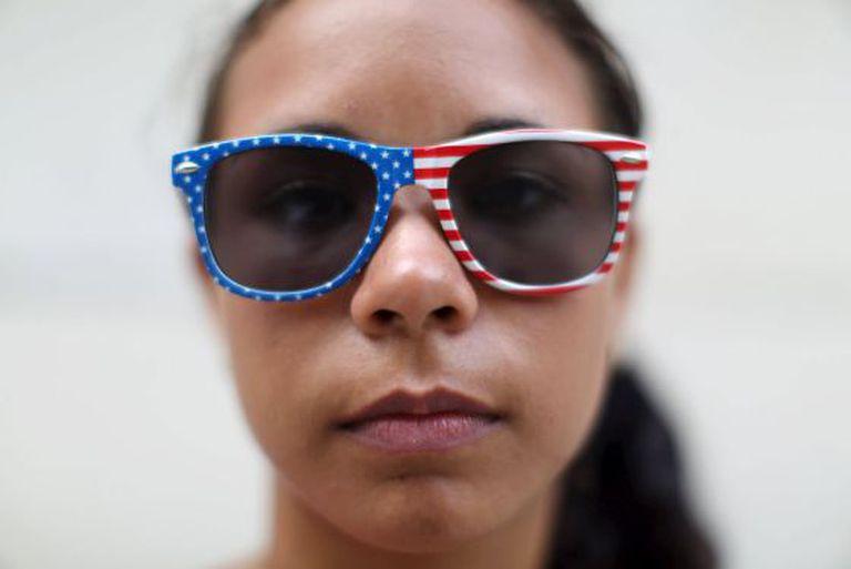 Estudante cuba posa em Havana com óculos enfeitados com a bandeira dos EUA.