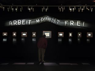 """Sala da exposição com o cartaz da entrada do campo de Auschwitz, no que se lê """"O trabalho liberta""""."""
