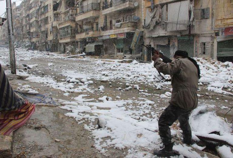 Um rebelde aponta seu rifle em uma rua de Alepo, na Síria.