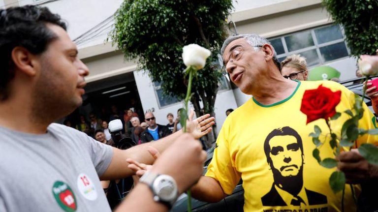 Um eleitor de Fernando Haddad oferece uma flor a um eleitor de Jair Bolsonaro, durante a jornada de segundo turno em um colégio eleitoral de São Paulo.