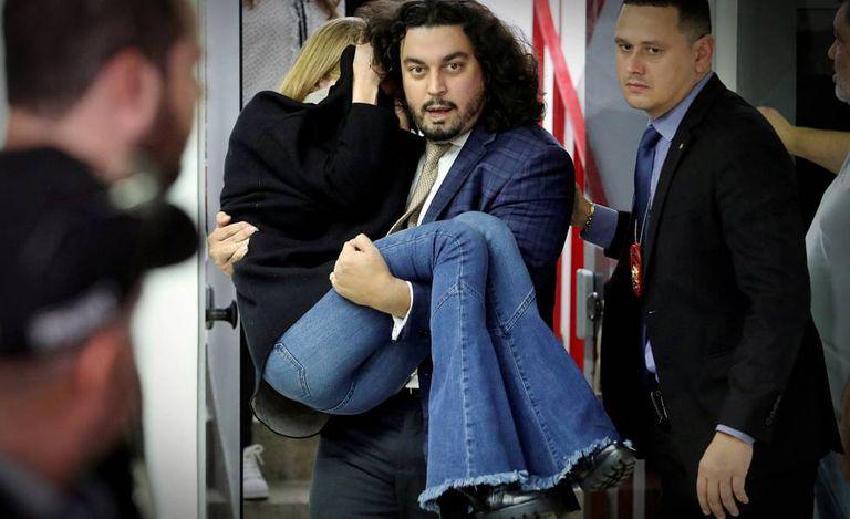 Danilo Garcia de Andrade carrega Najila após depoimento em São Paulo.