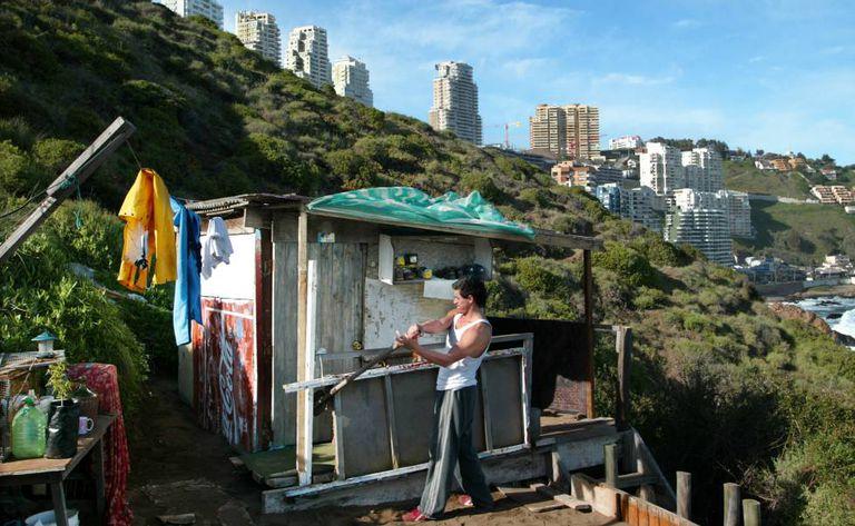 O chileno Marco Henrique, de 40 anos, conserta o barraco onde vive há 15 anos, num morro de Viña del Mar
