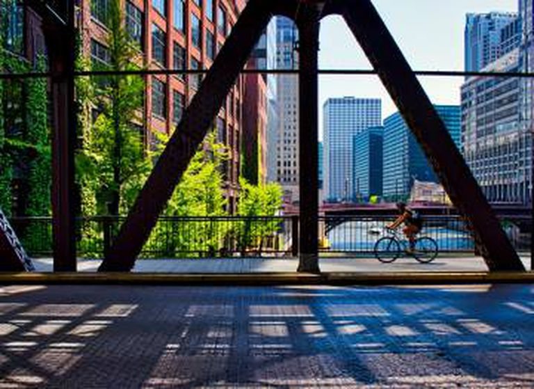 Ciclista cruzando uma rua do 'Loop', em Chicago (EUA), com o rio homônimo em segundo plano.