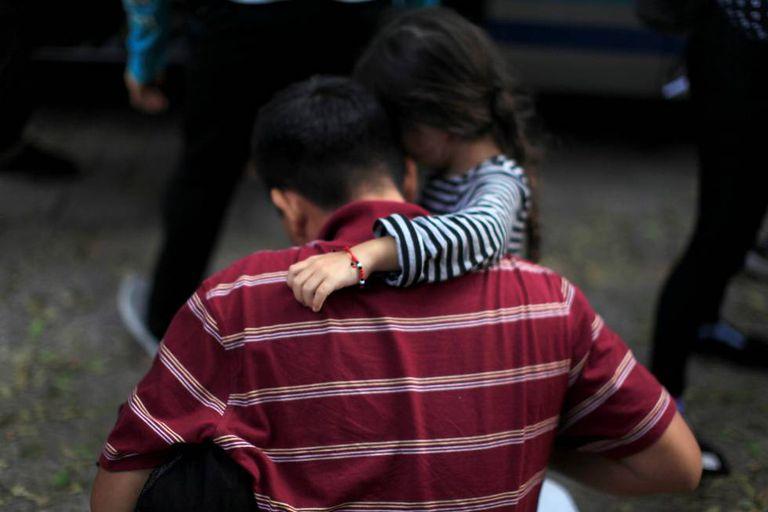 Menina abraça seu pai após sua deportação do México a San Salvador.