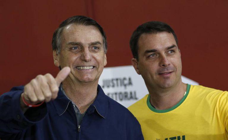 Flávio Bolsonaro ao lado do pai.