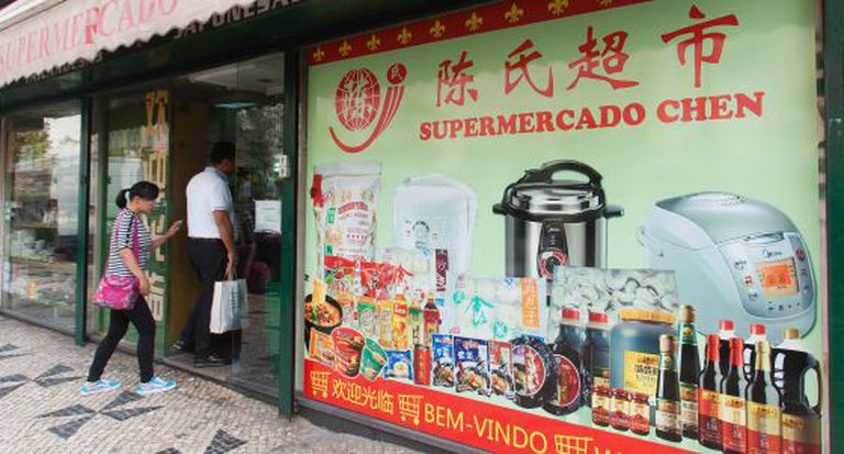 Consumidores entram em supermercado chinês em Lisboa.