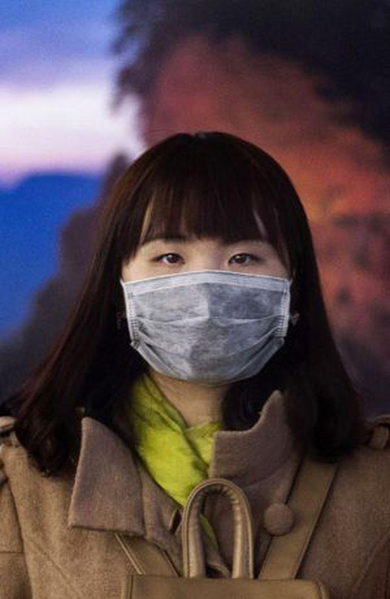 Mulher chinesa, com uma máscara para se proteger do ar poluído, no último 20 de novembro em Pequim.