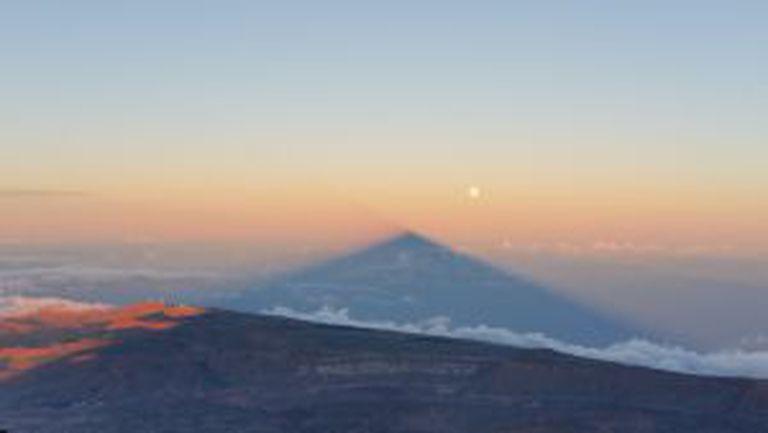 A sombra do vulcão se projeta na atmosfera, ao lado da superlua, deixando o Observatório do Teide à esquerda.