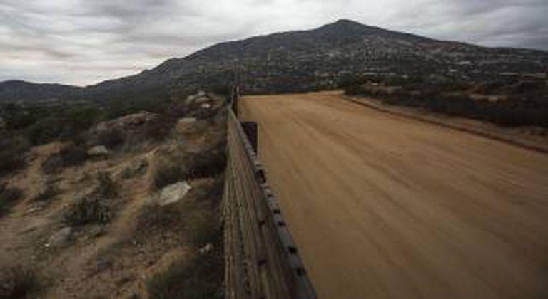 Muro em Tecate. Ao fundo o morro Cuchumá, colina sagrada dos Kumiai.