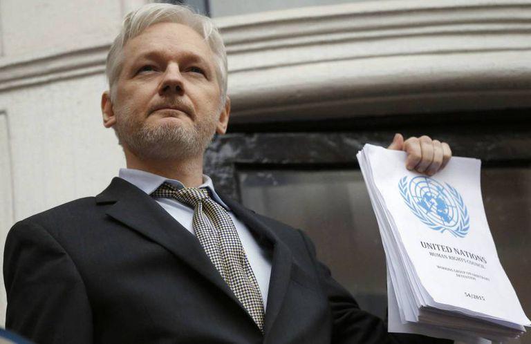 Julian Assange segura um relatório da ONU na embaixada de Equador.