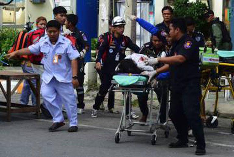 As equipes de resgate tailandeses assistem a uma vítima ferida.