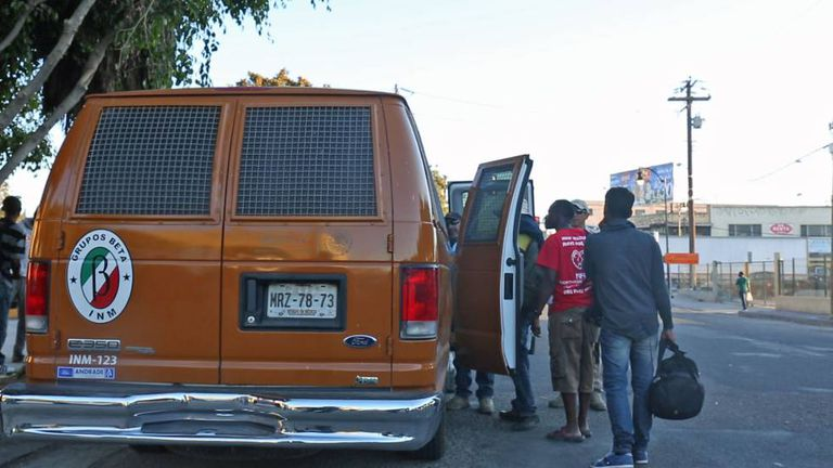 Um grupo de haitianos é atendido pelo serviço de imigração.