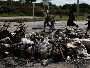 Uma família de venezuelanos passa pelos seus objetos pessoais incendiados por brasileiros na fronteira de Pacaraima (Roraima).