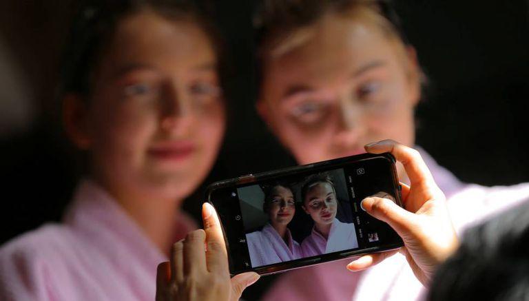 Modelos posam para foto tirada com celular.
