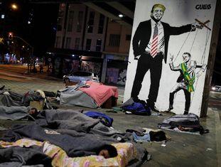 Moradores de rua descansam em frente a um grafite representando Bolsonaro e Trump.