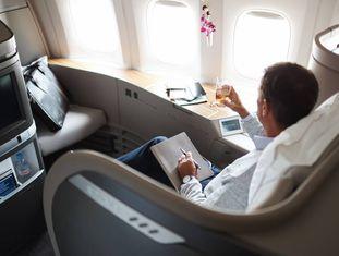 Um passageiro em um assento de primeira classe de Cathay Pacific Airways.