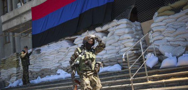 Um miliciano passa pela entrada de uma delegacia ocupada por ativistas pró-Rússia em Slaviansk.