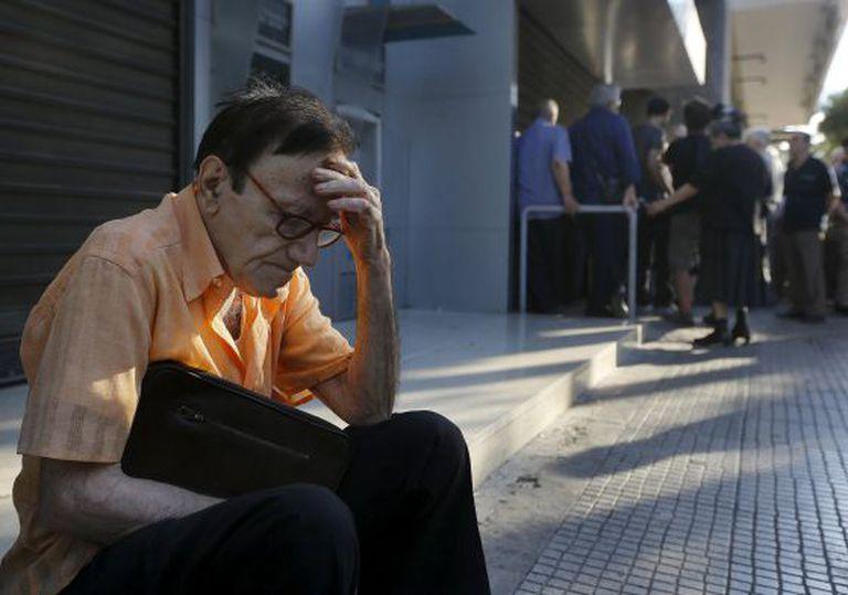 Aposentado grego descansa junto a agência bancária fechada. Muitos correntistas se aglomeravam nos bancos desde o começo da manhã.