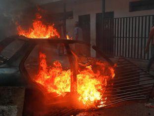 Um manifestante passa junto a um carro em lumes utilizado como barricada.