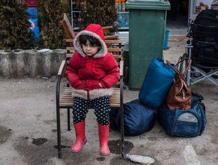Criança espera sentada em frente a um campo de refugiados na Sérvia.