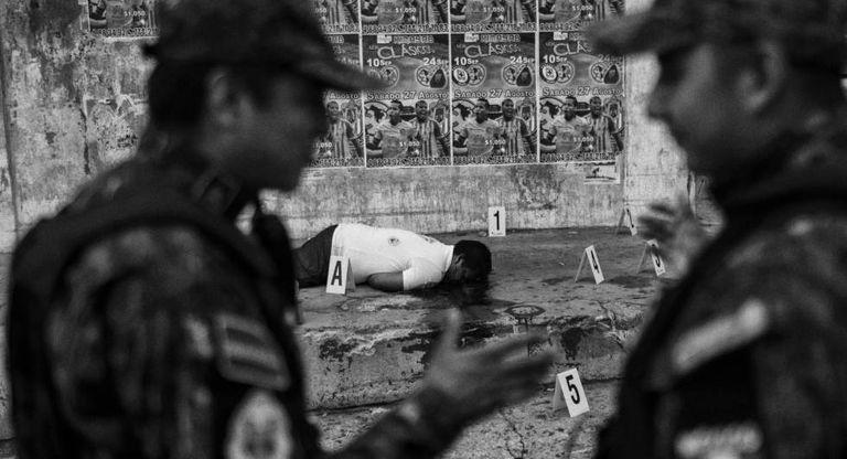 Policiais mexicanos juntos a um cadáver em Acapulco, a cidade com uma das maiores taxas de homicídios.