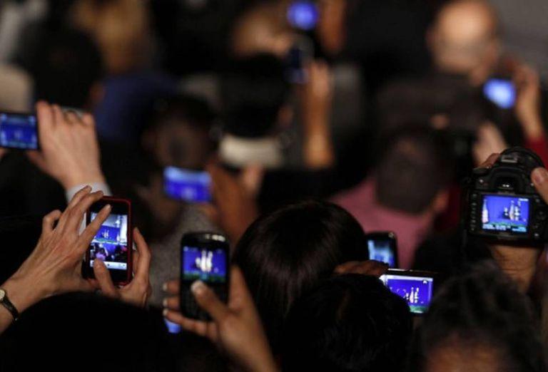 Grupo de pessoas grava vídeos com seus celulares.
