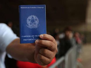 Homem em busca de trabalho mostra carteira de trabalho em 20 de março.