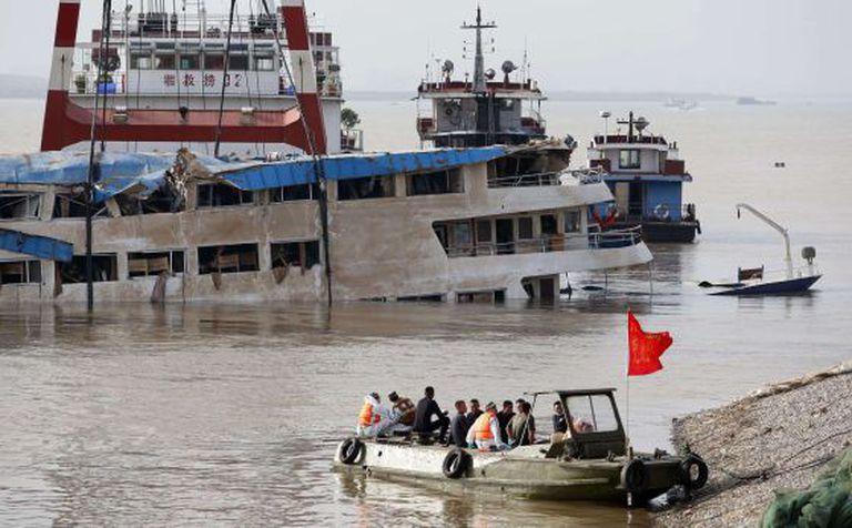 Trabalhadores sobre o barco que naufragou, depois de endireitá-lo.