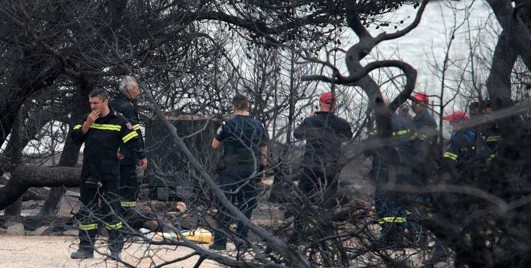 Bombeiros junto aos cadáveres carbonizados em Mati.
