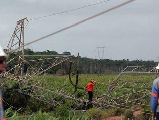 Técnicos ao lado de torre de transmissão de energia destruída no Ceará.