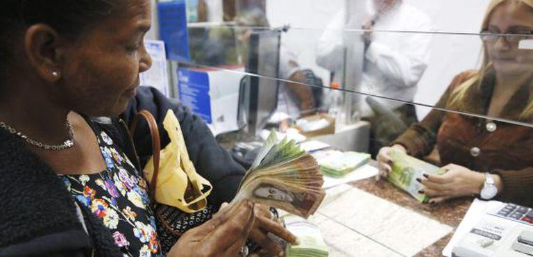 Uma mulher troca bolívares por dólares em Caracas, em fevereiro.