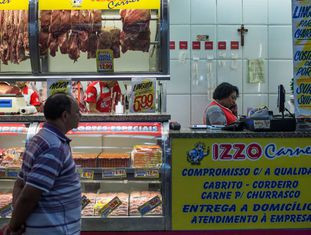 Homem olha carnes em mostrador em São Paulo.