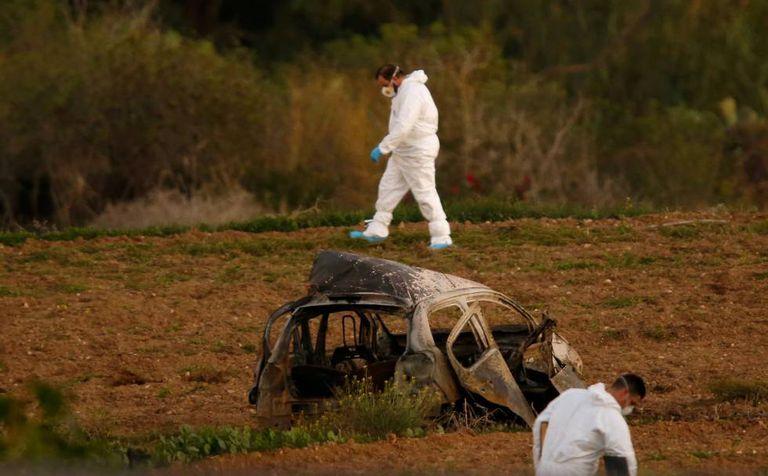 Peritos legais junto ao veículo queimado de Caruana Galizia em 16 de outubro em Bidnija, Malta.