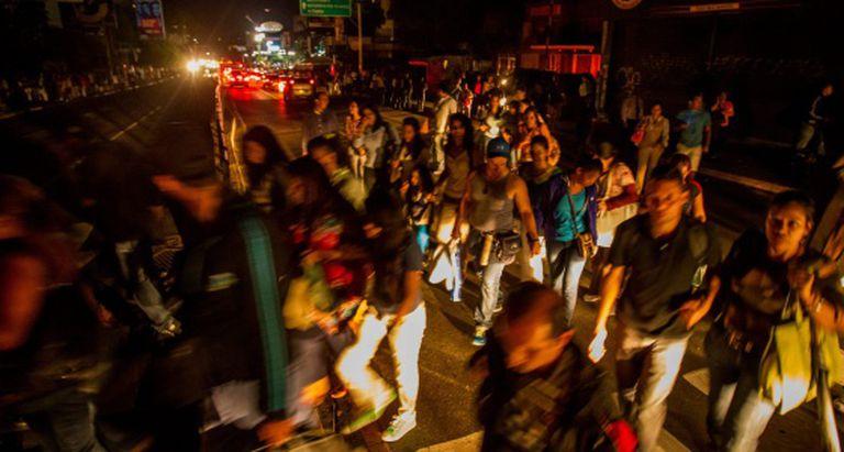 Pedestres caminham em uma rua às escuras, em Caracas.