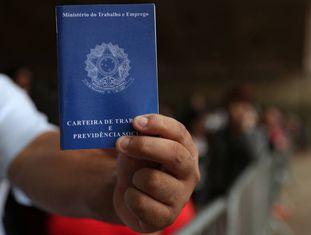 Um homem exibe sua carteira de trabalho enquanto aguarda na fila por emprego em São Paulo: idade mínima para aposentadoria deve ficar em 65 anos para homens e 62 para mulheres.